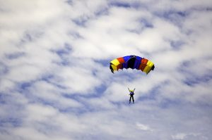 Man jumping with a colorful red, yellow and blue parachute captured against a cloudy autumn sky at an air show event.
